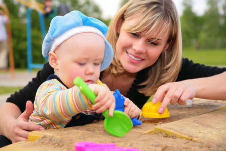 one parent: mother and child  play in sandbox