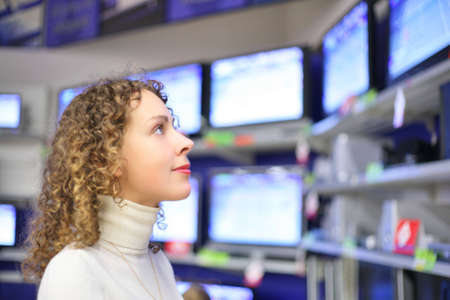 multiple choice: Young woman  looks at TVs in shop