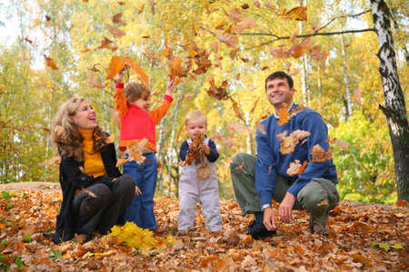 autumn in the park: family throw autumnal leaves Stock Photo