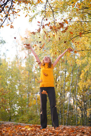 Beauty blond throws leaves in the park in autumn photo