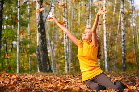 Beauty blond girl throws leaves in the park in autumn photo