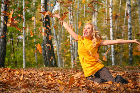 Beautiful blonde scatters leaves in wood in autumn photo