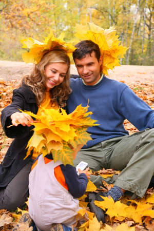 Pair and child with maple leaves on head in autumn wood photo