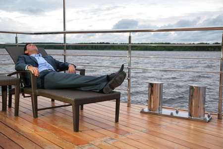 man in suit, who rests in chaise lounge on  wharf near water photo
