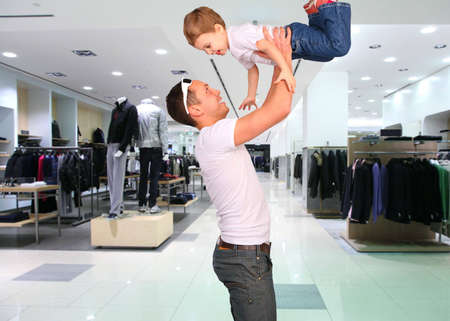emporium: father with child on hands in clothes shop Stock Photo
