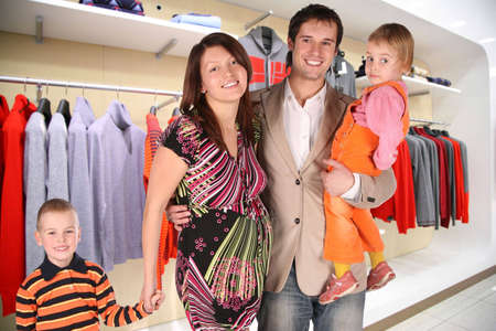 family with twio children and pregnant mother in Clothes store photo