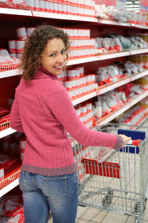 Woman in shop is standing half-turned, smiles photo