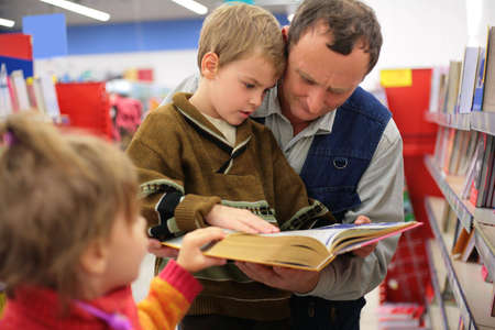 bookshop: Grandfather and grandson and little girl read the book in a bookshop