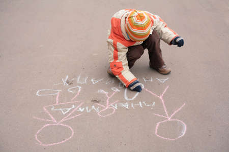 Boy sketches by chalk on asphalt Stock Photo - 5290718