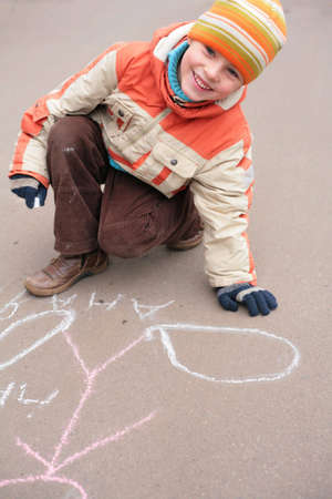 Boy drawing by chalk on asphalt photo