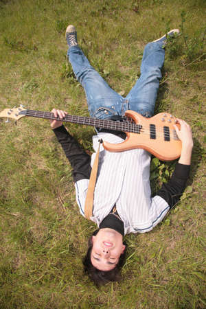 young man  lies with guitar on grass photo