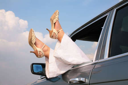 heelpiece: Female feet in window of car