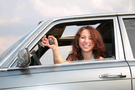 Girl in window of car with  key Stock Photo - 5353456