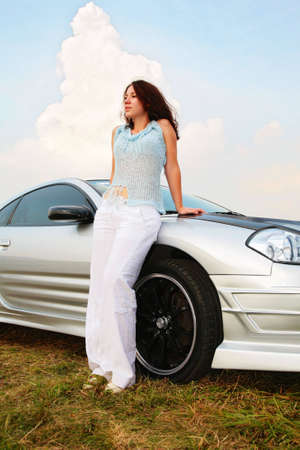 leant: Woman stands having leant on a sport car