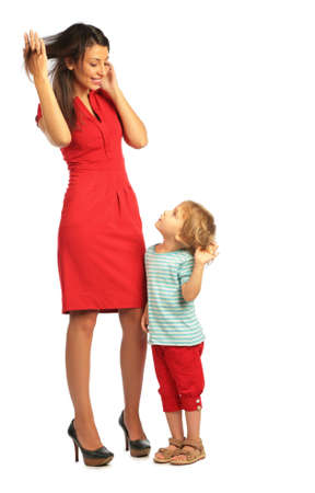 Little girl stands with a woman in red dress and touching hairs Stock Photo
