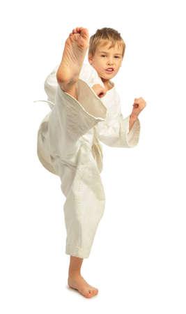 elementary age boy: Karate boy kick a leg Stock Photo