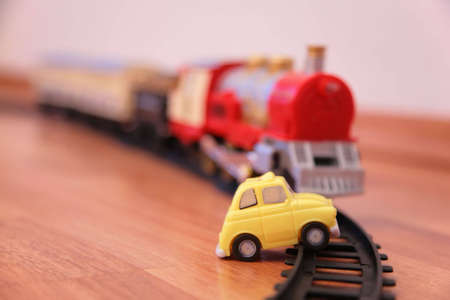 maquina vapor: Tren de juguete rojo y coche de juguete amarillo en ferrocarril