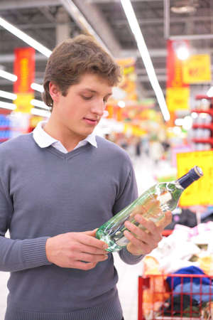 wine trade: Young man in supermarket with bottle of alcohol Stock Photo