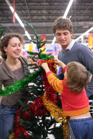 Parents with child  buys Christmas-tree with decorations  photo