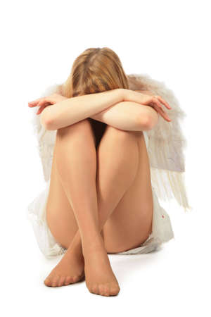 girl in angels costume sits face in knees and having closed by hands photo
