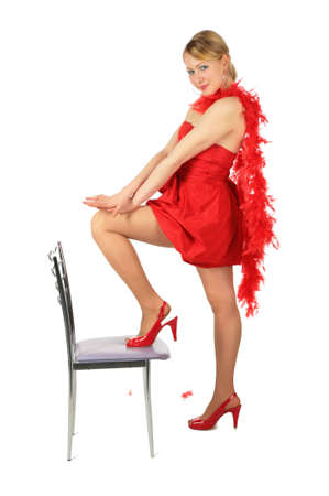 Young blonde girl in red dress and shoes puts leg on chair photo