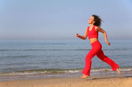 Young woman runs on shore of sea photo