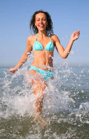 Young woman runs on water in sea photo