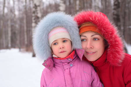 Mother with child in wood in winter photo