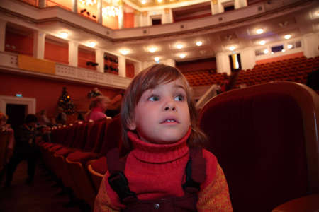 viewers: Little girl sits in theater