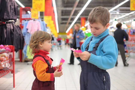 candy store: Children with sweetmeats in supermarket, focus on little girl Stock Photo
