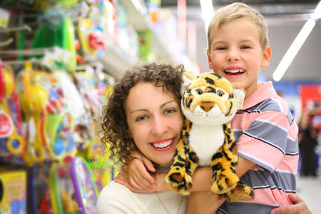 Mother and son with soft toy in shop photo