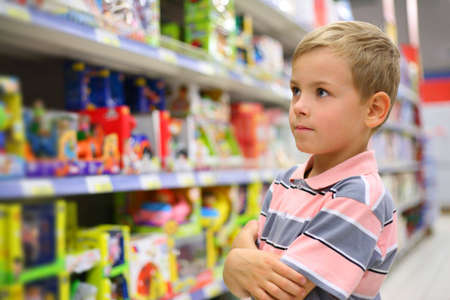 Boy looks at shelves with toys in shop Stock Photo