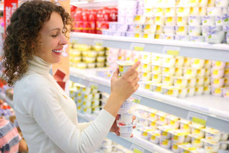 supermarket shelves: Young woman with yoghurt  in shop Stock Photo