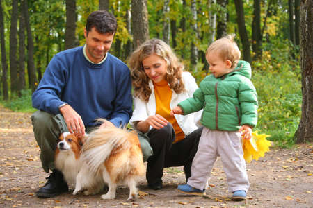 family with boy and dog in autumn wood photo