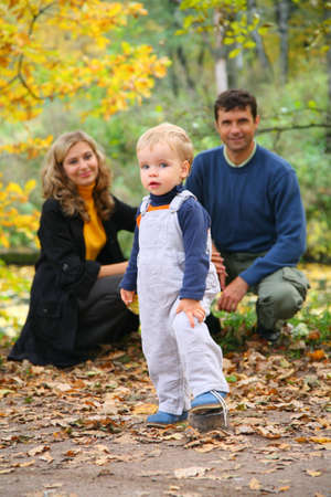 boy with untied lace and parents in autumn park photo