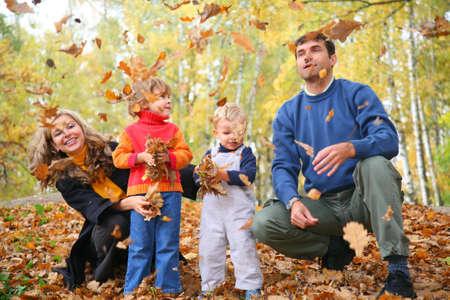 family of four throw autumnal leaves photo
