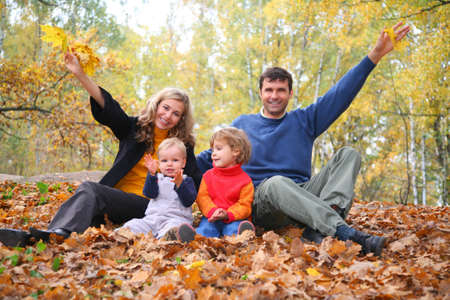 family of four sits in autumn park. parent hands up. photo
