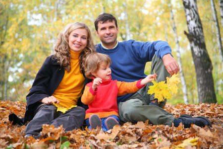 family gardening: family with little girl in autumn park