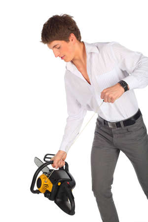 Young man starts chainsaw photo