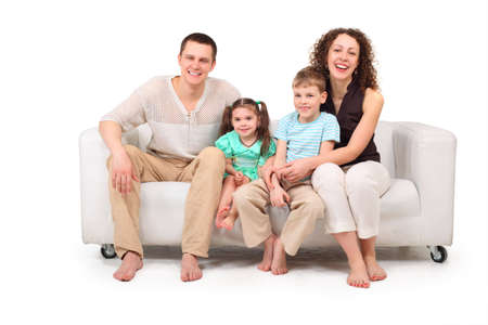 boy barefoot: Family with two children sitting on white leather sofa