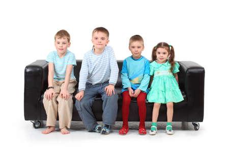 Four children sitting on black leather sofa photo