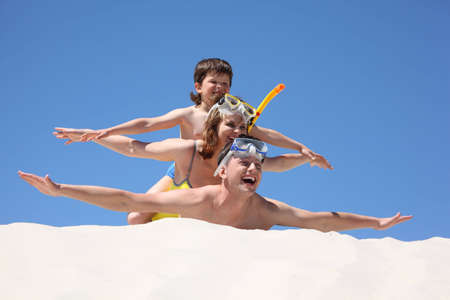 family with son lying on sand with hands up photo