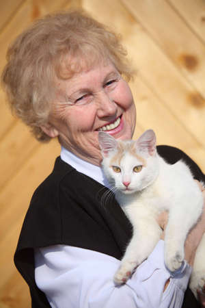 healthy seniors: Smiling aged woman with cat on hands, focus on cat Stock Photo