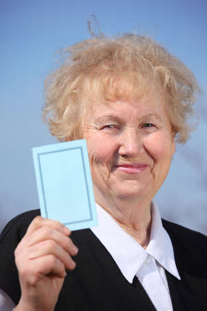 Aged woman holds card in hand on sky photo