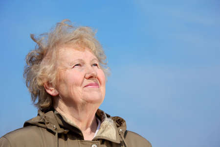 Smiling aged woman look in sky photo