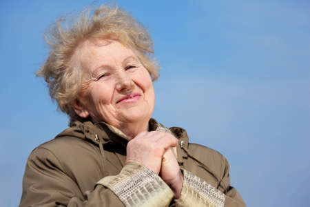 Smiling aged woman with hands on sky Stock Photo - 5361236