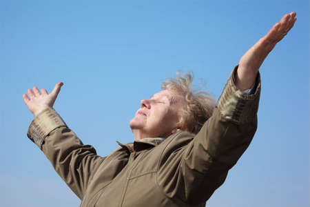 grizzle: Elderly woman with rised hands on sky Stock Photo