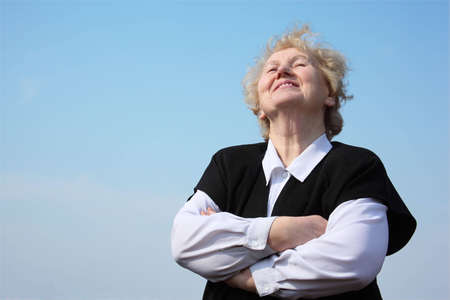 Elderly woman with crossed hands on sky photo
