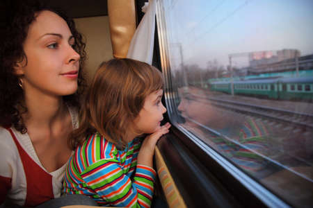 fast train: mother and daughter look in train`s window Stock Photo