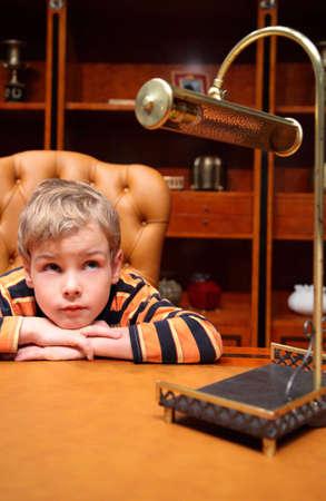 Boy sits in luxury office photo
